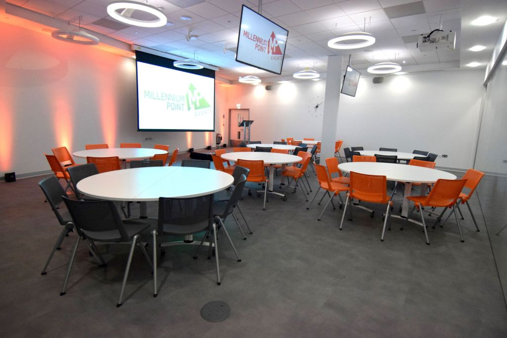 Large meeting room with white walls and five round tables each with seven chairs