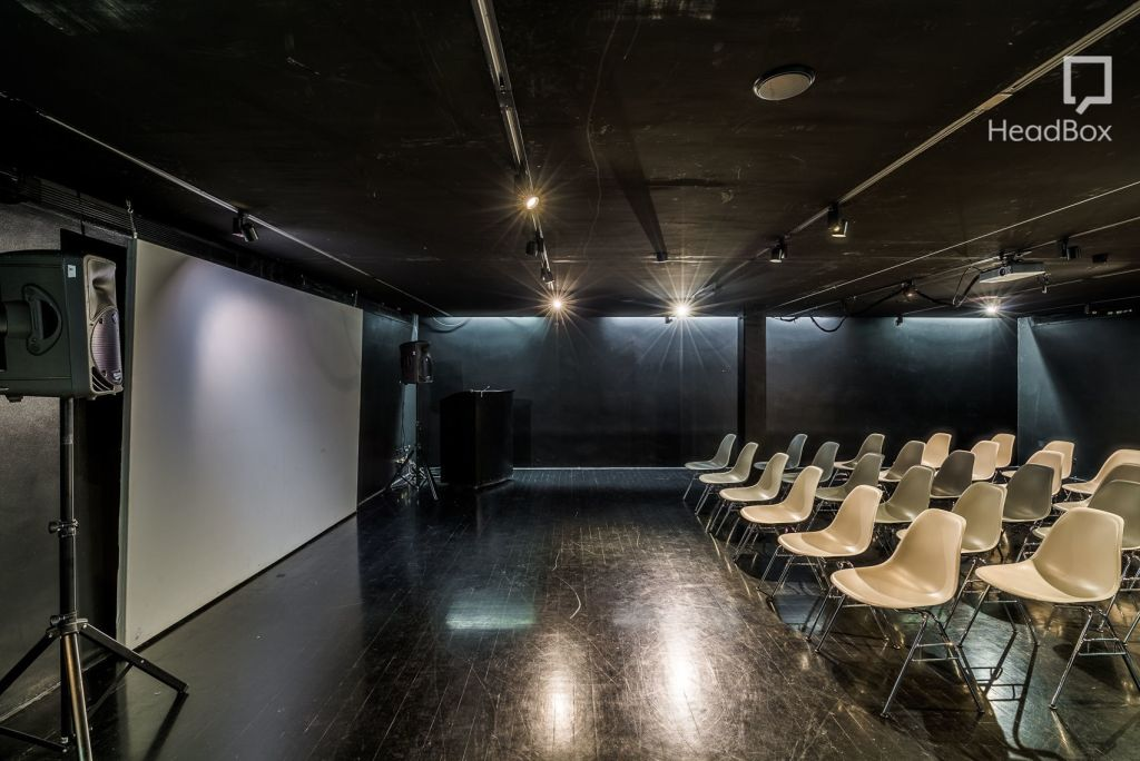 A cheap venue hire in Bristol. A rectangle Space that has black walls and rows of white chairs