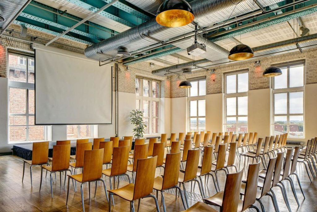 industrial style conference space with rows of wooden chairs facing a projector screen