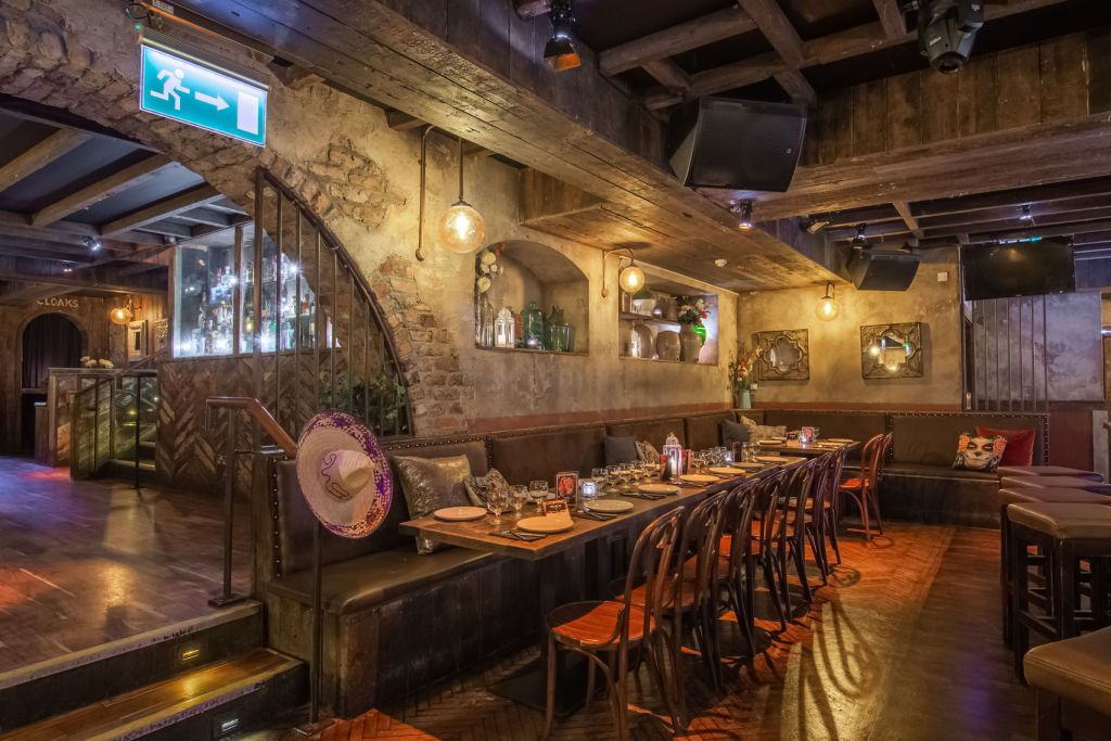 party venue with exposed brick walls, wooden tables, chairs and booths with steps leading to bar area