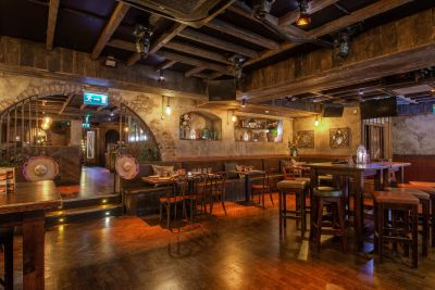 Underground bar with wood tables and chairs.