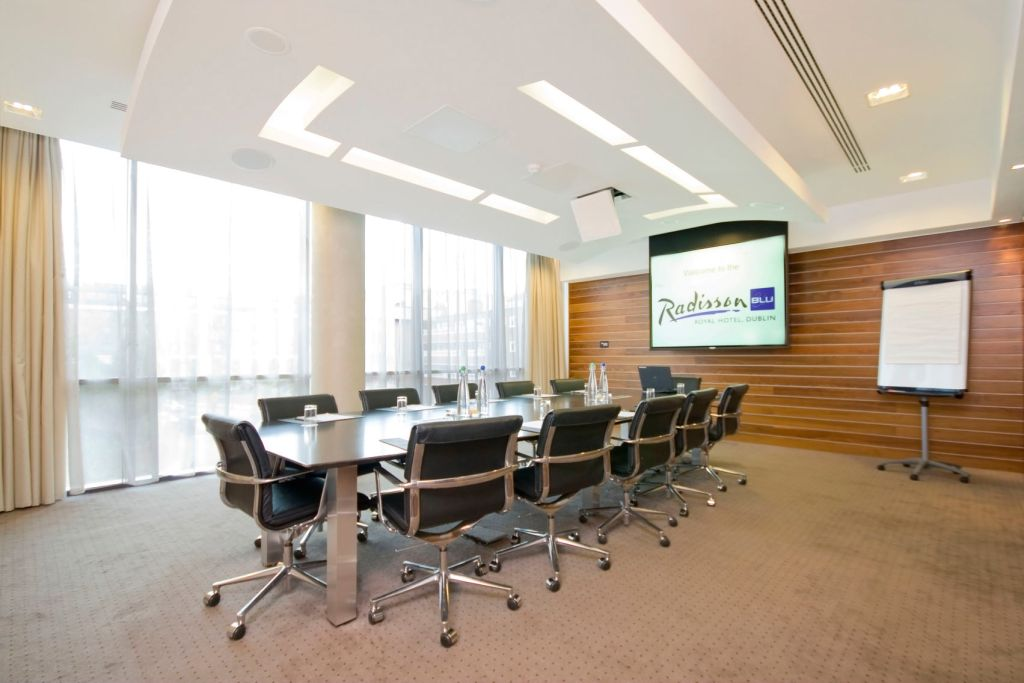 boardroom with long table and leather chairs facing a TV screen