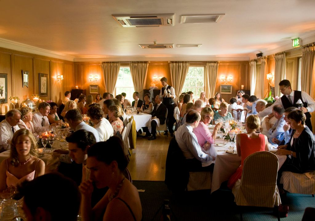 Dining room with groups of guests sat at tables