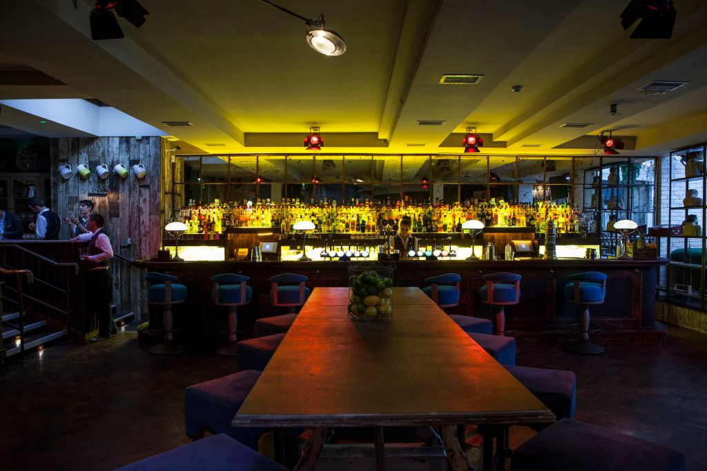 Private bar with long wooden table and stools at the bar