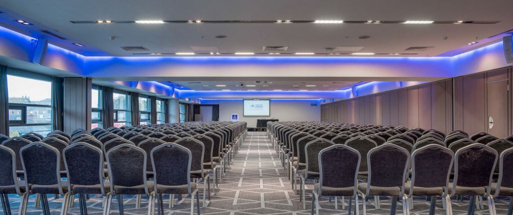 large conference room with rows of metal chairs facing a tv screen