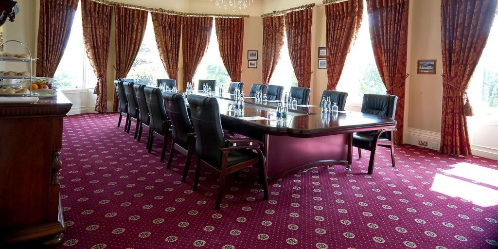Boardroom with long wooden table with leather chairs on red carpet with long windows and red curtains