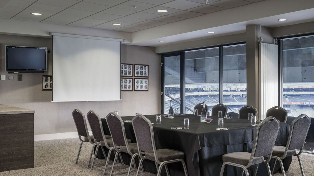 meeting room with large table facing a projector with large windows overlooking sports stadium