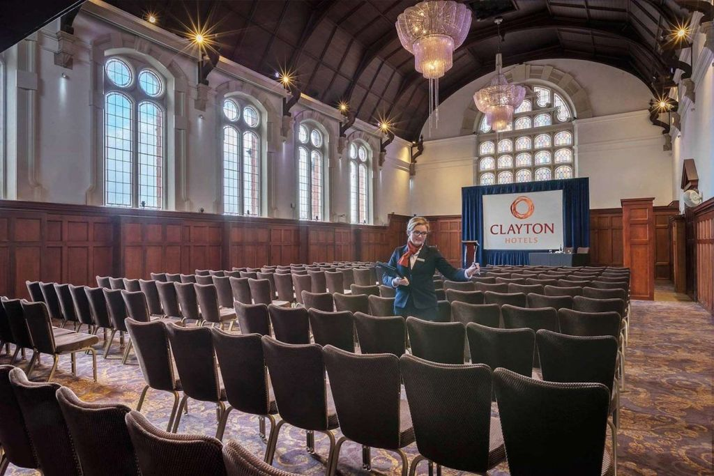 church hall with rows of brown leather chairs facing a projector screen