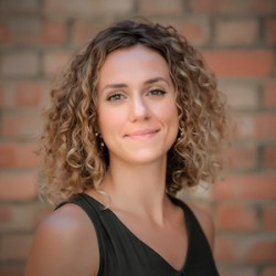 A headshot of a woman with curly hair