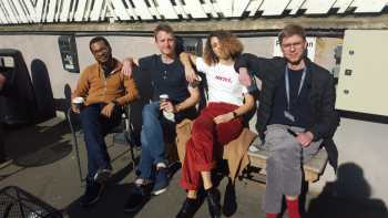 4 people sat on a bench with coffee
