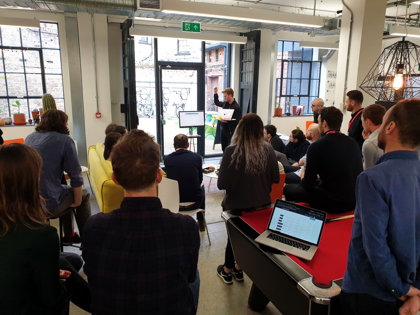 A group of people watching a man give a presentation