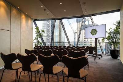 Small meeting room with brown chairs facing a tv screen looking out onto the city of london