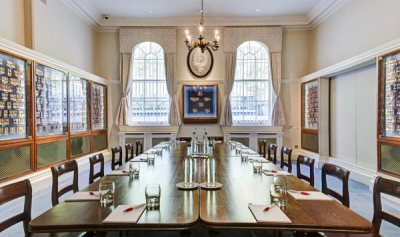 meeting room with long wooden table and medals lining the walls in glass cases