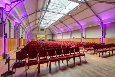 conference room with rows of red seats, purple lighting and a high arched ceiling