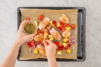 Person adding spices to a chicken and vegetables on a sheet pan