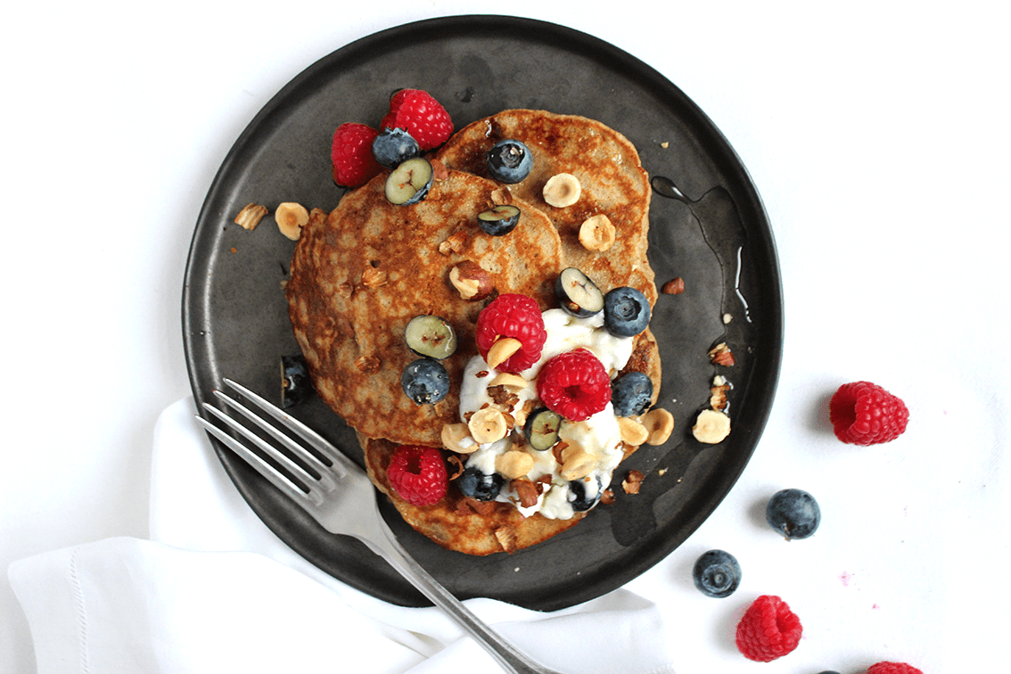 Fluffy banana pancakes with mixed berries and honey