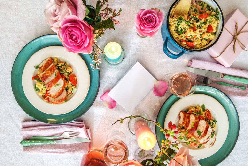 Romantic dinner table with proscuitto wrapped chicken dish