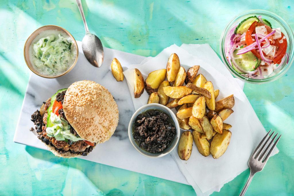 Souvlaki-Burger mit Oliventapenade, Kartoffelspalten und griechischem Salat