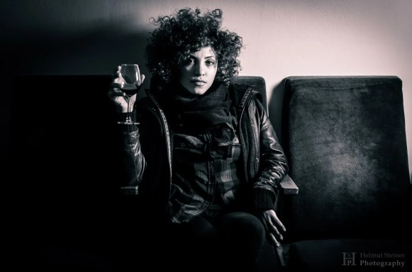 Young woman with curly hair holding a wine glass