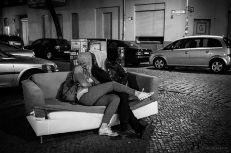 A couple kissing on an abandoned couch in the middle of the street in Berlin