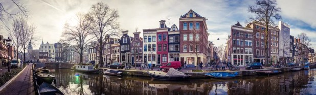 A panorama of a canal in Amsterdam showing leaning houses