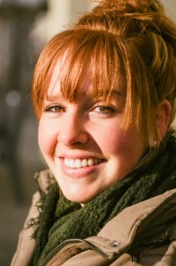 Portrait of a young smiling redhead with a green scarf
