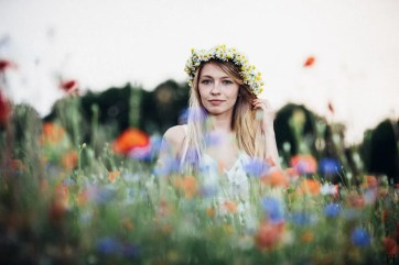 Portrait of a girl standing in a wild poppies field with a girdle of chamomile flowers