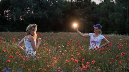 behind the scenes shot of a portrait shoot in a wild poppies field, girl with white summer dress, flowers
