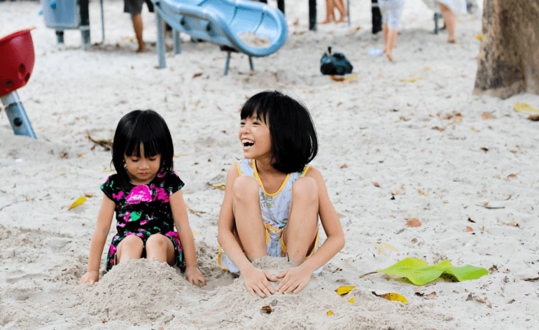 children playing on the beach, happy faces