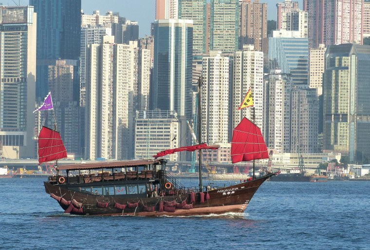 junk boat with red flag, hong kong skyline, tst harbour