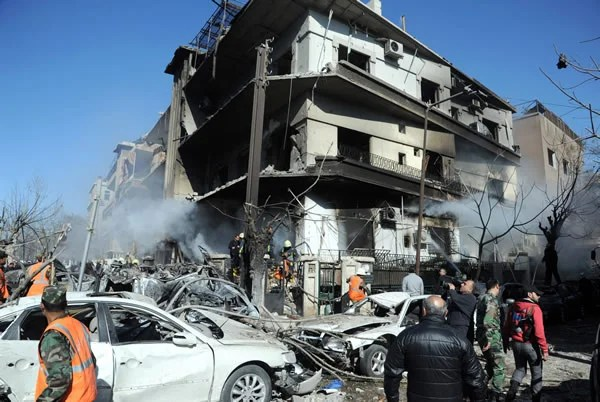 A handout picture released by the official Syrian Arab News Agency (SANA) on March 17, 2012, shows fire fighters at the scene following a two bomb attacks on security buildings in the heart of the Syrian capital Damascus which killed several people, state television said. AFP PHOTO/HO