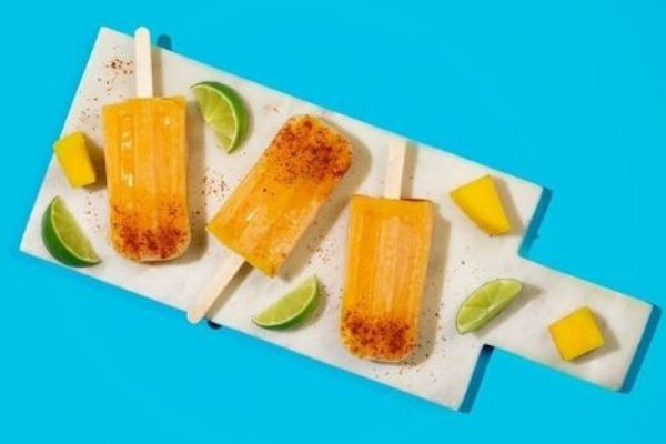 Tropical Mango Coconut Popsicles, lemon and lime, cococut oil,mango, mango popsicles, white board, bright yellow piopicles