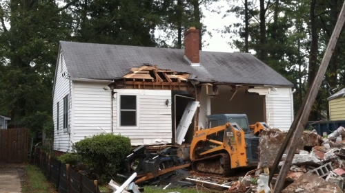 916 East Lake Drive with the front porch and part of the front facade demolished. A two-person crew deconstructed the house using a Mustang track loader and bare hands. As parts of the house fell away during the eight hours it took to reduce the building to a pile of rubble, interior spaces once called home by multiple families were laid bare.