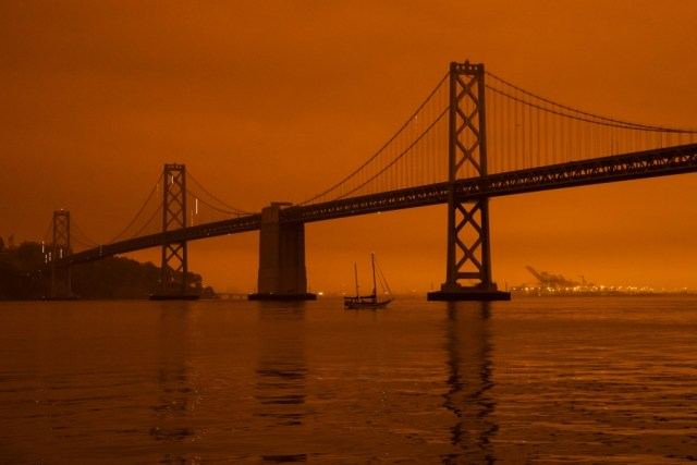 Bay Bridge, as smoke from various wildfires burning across Northern California mixes with the marine layer, blanketing San Francisco in darkness and an orange glow