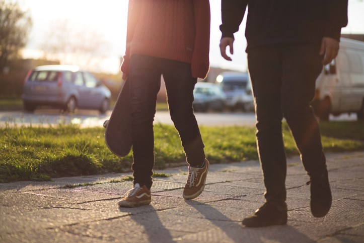 a couple walking on a sidewalk.