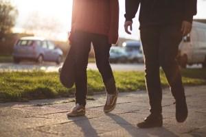 a couple walking on a sidewalk.