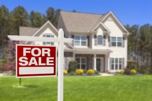 """White and beige home with a green lawn and a red """"for-sale"""" sign out front."""