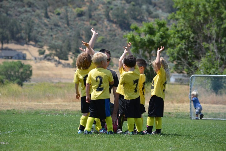 Young children high-fiving after a soccer game.