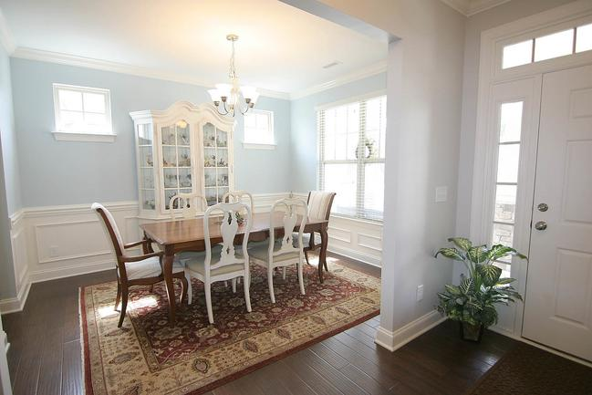 Fancy dining room area with crown molding and huge windows.