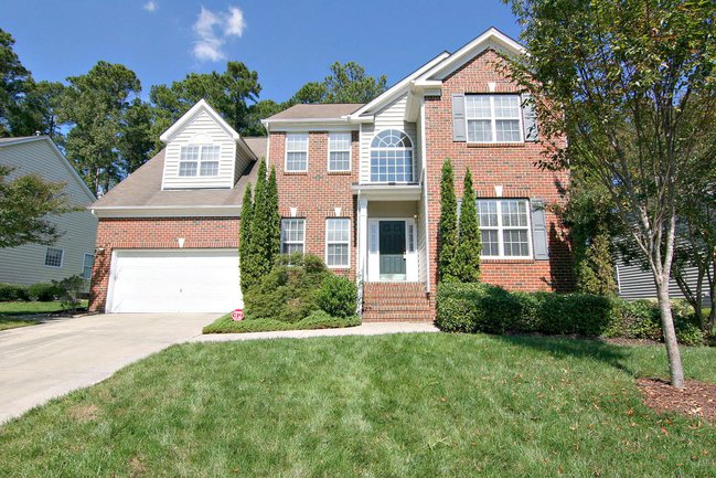 Large two-story brick home with a lush green lawn and large white garage.