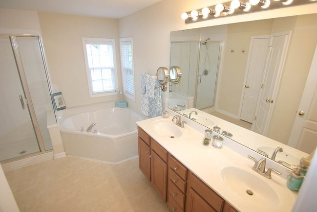 Large master bathroom with huge jacuzzi tub, double vanity, and large mirror.