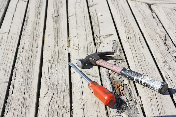hammer and screwdriver on rotting deck boards