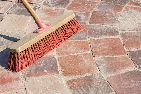 brushing sand into joint of pavers