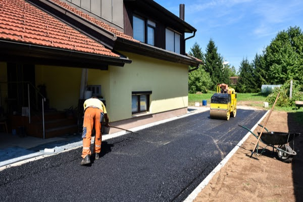 laying new asphalt driveway in summer