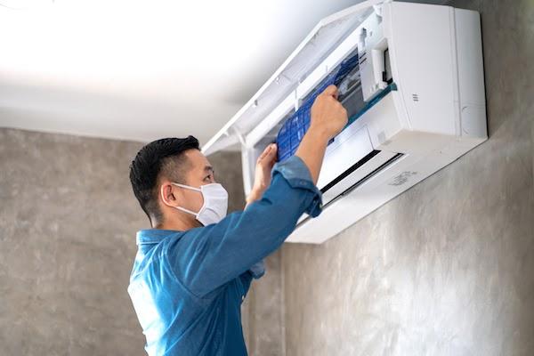 repair man fixing air conditioner