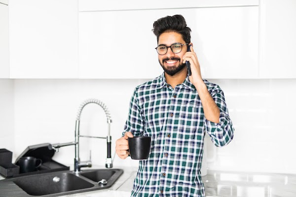 man using phone in kitchen