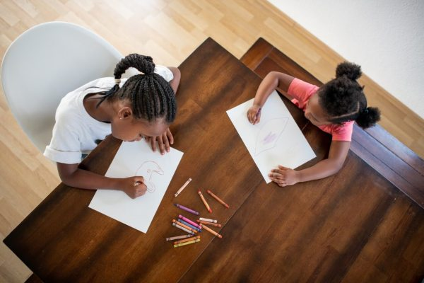 two children sitting at table colouring