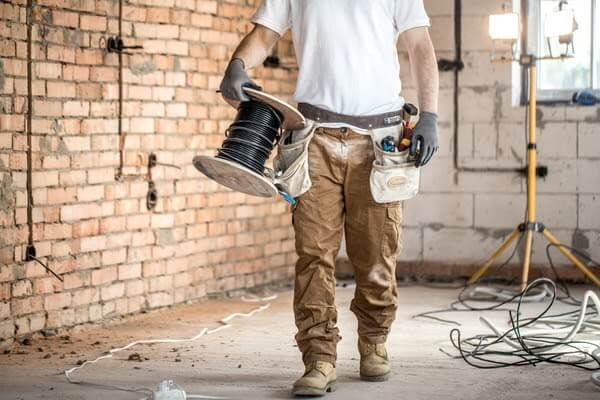 electrician walking with cables fixing knob and tube
