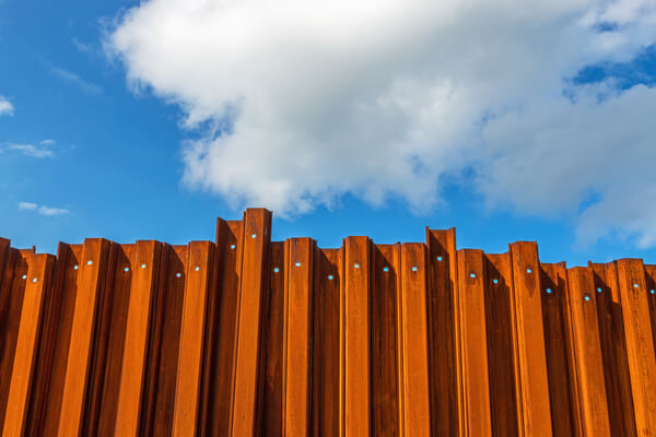 Tall rusty metal fence on the sandy beach with cloudy sky on the background
