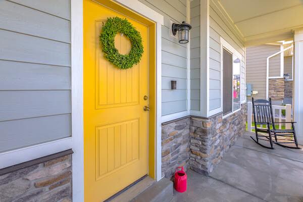 yellow front door with wreath